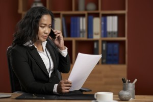 Female Asian lawyer reading contract and consulting client on the phone