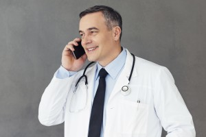 Mature male doctor talking on mobile phone with smile while standing against grey background