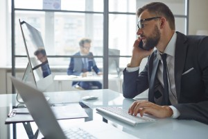 Modern businessman consulting partner by phone while sitting in front of computer in office