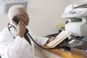 An African American senior male doctor holding document while using landline phone