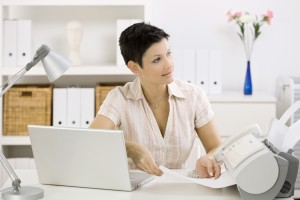 Woman using fax machine at home office. Click here for other Business images:
