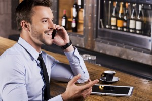 Side view of happy young man in shirt and tie talking on the mobile phone and gesturing while sitting at the bar counter