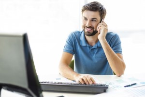 Photo of young, handsome, successful and confident businessman. Young businessman working with computer and talking on mobile phone. White modern office interior