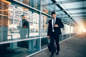 Businessman walking with luggage and using mobile phone at airport.
